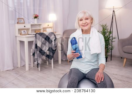 Important Hydration. Pleasant Elderly Woman Sitting On A Yoga Ball And Holding A Water Bottle While