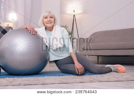 Pleasant Recreation. Charming Senior Woman Sitting On A Mat And Leaning On A Yoga Ball While Regaini