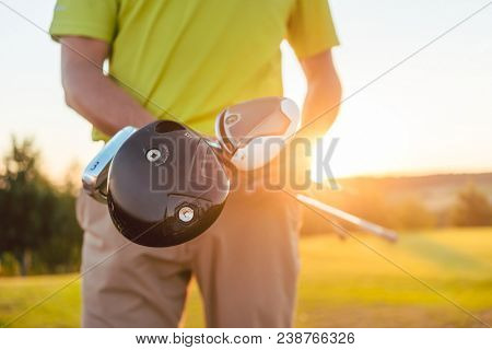 Close-up of the hands of a male professional player holding three different golf clubs, while standing against sunshine on the golf course of a modern country club