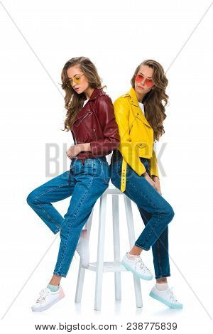 Attractive Stylish Twins In Leather Jackets And Sunglasses Sitting On Wooden Chair Isolated On White