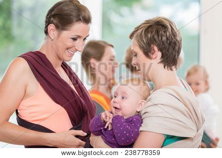 Young happy women learn how to use baby carriers for carrying children