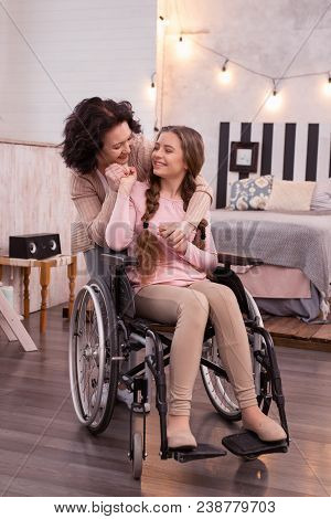 Stay Positive. Attractive Crippled Girl Using Wheelchair While Woman Laughing