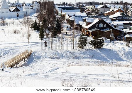 wooden urban houses and Pokrovsky Monastery (Convent of the Intercession) near riverbank of frozen river in Suzdal town in winter in Vladimir oblast of Russia poster