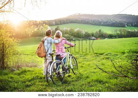 Beautiful Senior Couple Outside In Spring Nature, Standing With Bicycles On Grassland. Rear View.