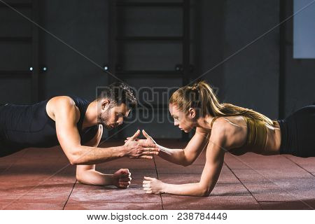 Young Athletes Giving High Five To Each Other While Doing Push Ups In Sports Hall