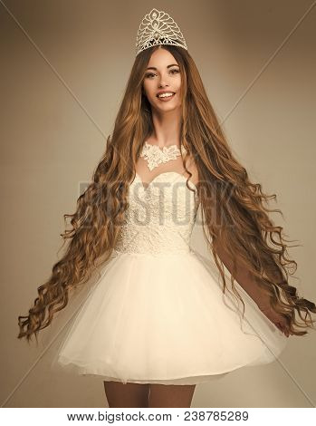 Girl Has Fashionable Makeup And Healthy Hair On Grey Background. Woman With Long Hair White Dress An
