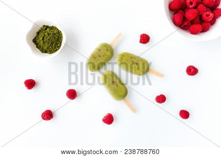 Three Matcha And Raspberry Popsicles On White Background With Matcha Powder And Fresh Raspberries In