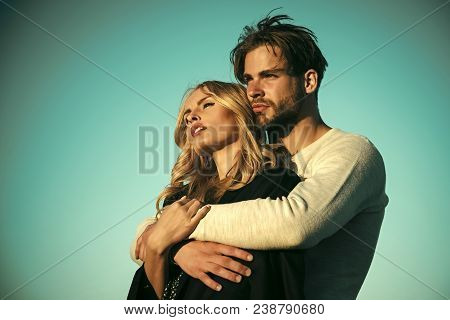 poster of Couple in love. Family couple of man and sexy girl, trust. Muscular man and woman with long blond hair, love. Relations of happy family, future. Couple in love on blue sky background. Love and romance.