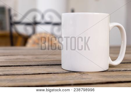 White Blank Coffee Mug Mock Set-up, Outside On A Little Wooden Table With An Ironwork Chair In The B