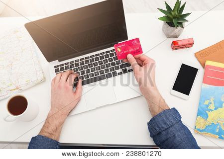 Booking Tickets Online On Laptop And Credit Card. Unrecognizable Man Preparing For Vacation, Holding