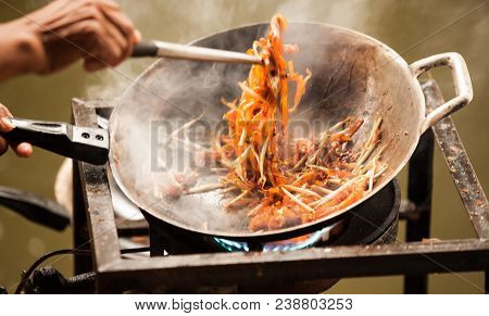 Thai Asian Street Fast Food In Hot Pan, Pad Thai, Or Phad Thai Is A Stir Fried Rice Noodle Dish Comm