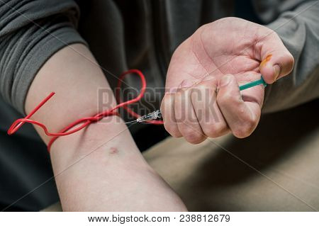 Man Vaccine Injecting  In His Arm. Drugs Concept. Disease Concept.  Drug Addict Man With Syringe Usi