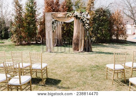 Arch For The Wedding Ceremony, Decorated With Cloth And Flowers. Ceremony Zone View