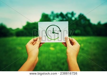Close Up Of Woman Hands Holding A White Paper Sheet With A Clock Ikon. The Infinity Of Time Symbol O