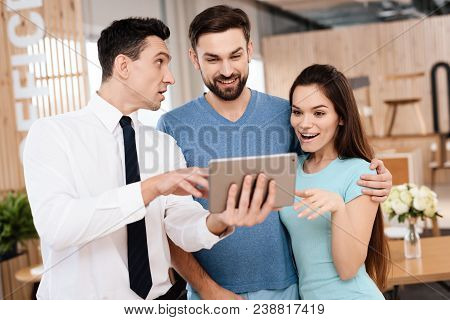 The Manager Of The Furniture Store Is Showing To The Guy And The Girl Examples Of Furniture Design O