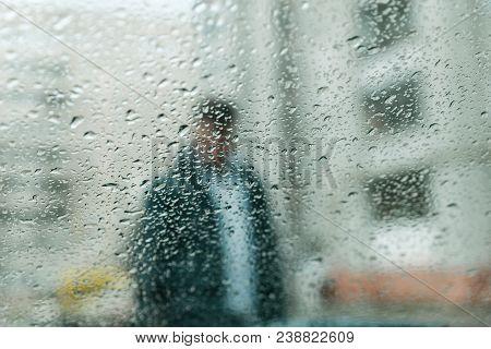 Wet Rain Drops On Glass. Man Silhouette Through Wet Glass