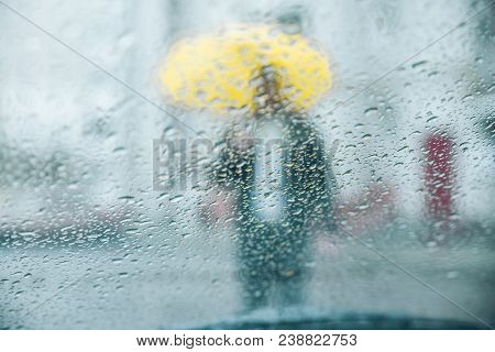 Wet Rain Drops On Glass. Man With Yellow Silhouette Through Wet Glass