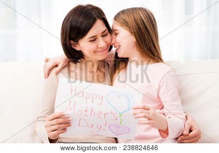Lovely little girl hugging her mother , Girl holding creative handmade greeting card for mother. Daughter congratulates mom and gives her postcard for Happy Mother's day