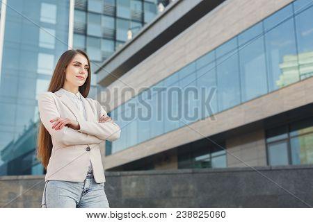 Portrait Of Thoughtful Confident Caucasian Businesswoman Against Modern Glass Office Center Backgrou