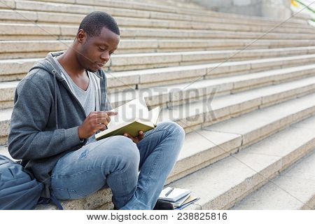 Young Serious African-american Man Reading Book, Sitting On Campus Stairs, Studying And Preparing Fo