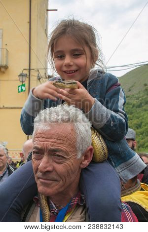 Cocullo, Italy - May 1, 2018: Beautiful Little Girl Caressing A Big Snake At The Serpari Feast In Co
