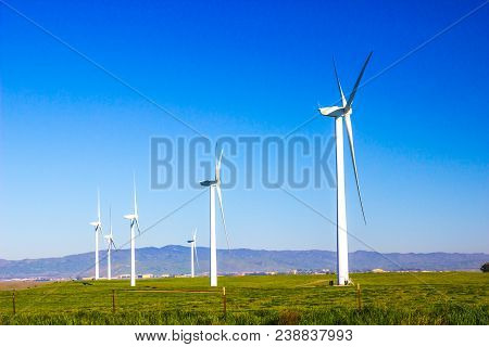 Row Of Three Bladed Energy Producing Windmills In Field