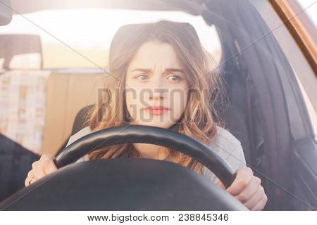 Nervous Female Driver Sits At Wheel, Has Worried Expression As Afraids To Drive Car By Herself For F