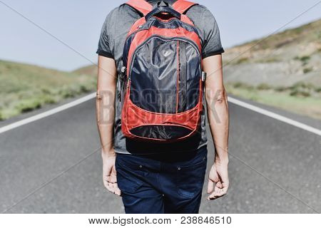closeup of a young caucasian man, seen from behind, carrying a backpack walking by a secondary road