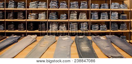 Jeans Pants On The Store Shelf. Blue Jeans Denim Collection Jeans Stacked.