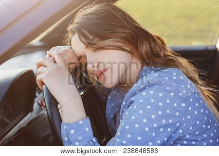 Exhausted Overworked Female Driver Can`t Drive Car Any More, Naps On Wheel, Feels Sleepy And Tired,