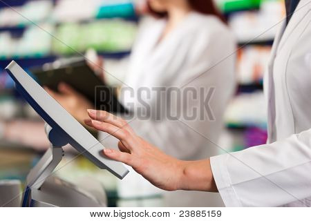 Pharmacist with female assistant in pharmacy standing at the cash point