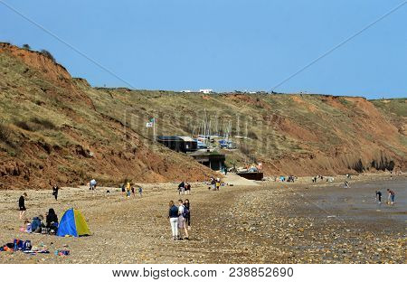 FILEY, NORTH YORKSHIRE, ENGLAND - 23rd April 2018: Tourists relaxing on Filey town beach with Brigg in background on the 23rd April 2018. This is a popular tourist destination.