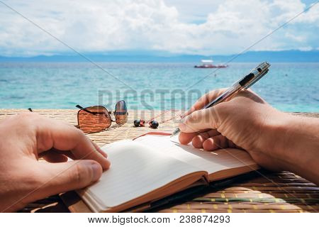 Person Writing On Notebook In Front Of The Beach. Summertime. Writer. Travel Bucket List.