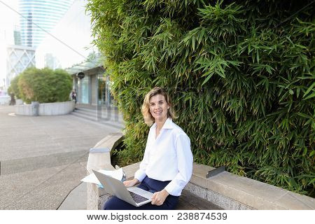 Secretary Working With Laptop And Papers In Open Air Near Green Plant. Concept Of Busines, Modern Te