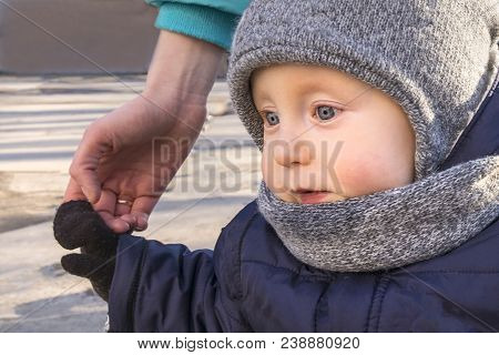 Nice Interested Kid In Beautiful Warm Cap Scarf And Jacket Going For Walk Holding Mom Hand. Concept
