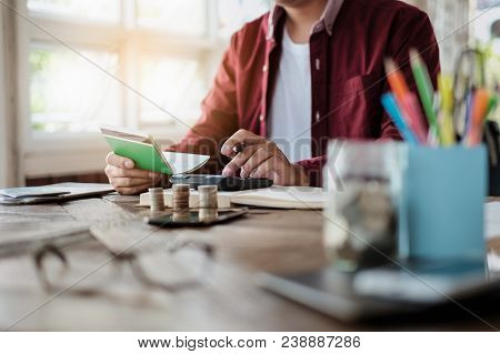 Business Man Hands Holding Saving Account Passbook With Calculator, Account And Saving Concept.