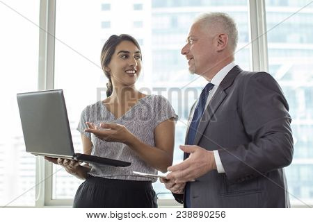 Two Experts Sharing Experience After Business Seminar. Young Indian Woman With Laptop And Mature Man