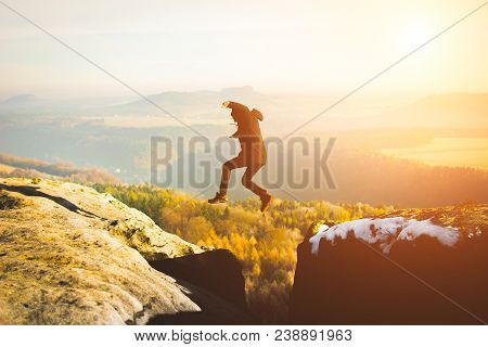 Person Jumping On Mountain Cliff During Daytime