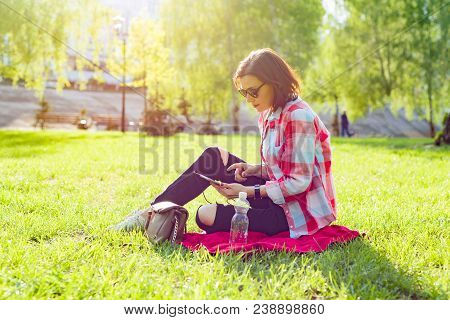 Adult Middle-aged Woman Sits In City Park On The Grass. In Headphones Listens Audio Book, Watches Vi