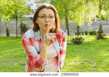 Outdoor Portrait Adult Woman Shows Sign Quietly, Secret, Holds Finger Near Her Lips. Background City