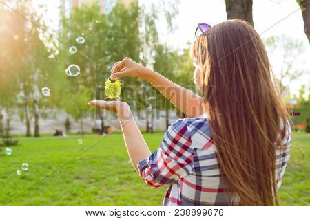 Young Woman Holding Alarm Clock In Her Hand, Looking At The Time. Background Sunny City Park, Copy S