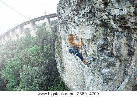 Woman Rock Climber Climbs On The Cliff. Rock Climber Climbs On A Rocky Wall. Woman Makes Hard Move