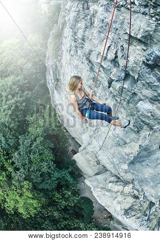 Woman Rock Climber Climbed On The Cliff. Rock Climber Climbed On A Rocky Wall. Woman Descends From A