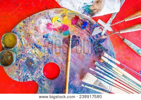 Background Image Of Color Paints On Art Palette With Paint Brushes And Palette Knives