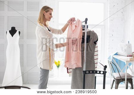 Individual Design. Pensive Female Couturier Standing While Holding Garment
