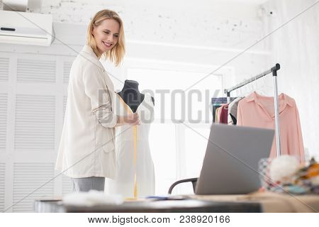 Online Lecture. Glad Female Couturier Using Meter While Gazing At Screen