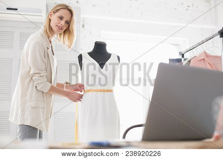 Online Life Hacks. Jovial Female Couturier Using Meter While Staring At Screen