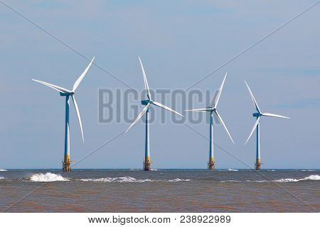Wind Turbines At Sea. Suistainable Resource Offshore Windfarm. Four Large Renewable Green Energy Tur