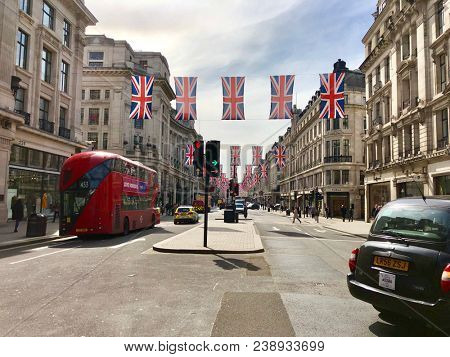 REGENT STREET, LONDON - MAY 3, 2018: Traffic moves below hanging Union Jack flags on Regent Street in central London, UK.