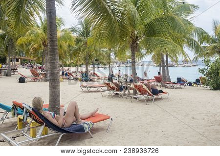 Blue Bay, Curacao - April 11, 2018 - People In Their Beach Chairs Sunbathing At Blue Bay Resort